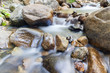 Clear water of stream flowing through natural mountain rocks.