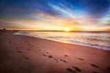 Fototapety Footprints along a Maine beach as sun comes over the horizon