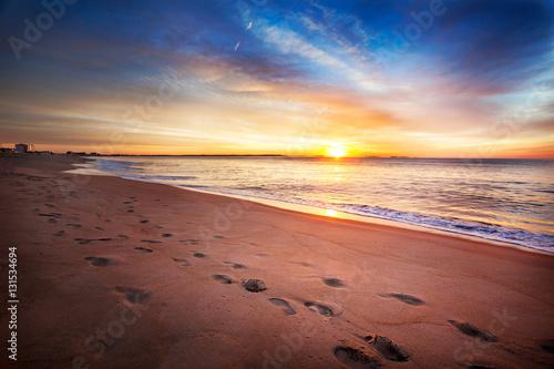 Footprints along a Maine beach as sun comes over the horizon Poster