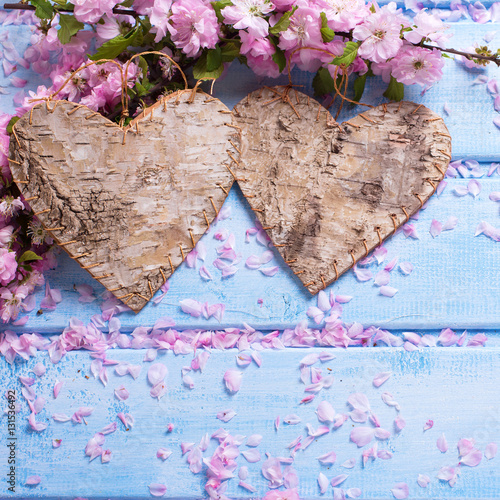 Poster Two decorative  hearts and pink sakura flowers  on blue wooden b