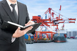 Businessman writing notebook with commercial delivery cargo cont