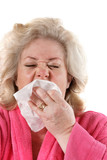 Older woman sneezes into a tissue