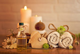 Spa and wellness setting with oil, candles and towels
