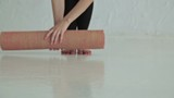 Woman rolls apart yoga mat in fitness studio. Freedom, health and yoga concept. Close up shot