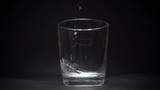 Mineral water in a transparent glass in slow motion