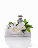 stones in bottle and gardenia on towel –white background