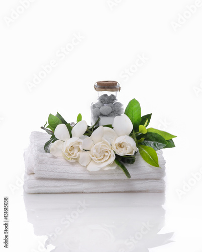 Fotobehang Spa stones in bottle and gardenia on towel –white background