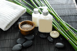 White towel and stones and oil,grove on bamboo mat