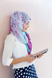 Muslim woman standing , holding tablet computer. - 131615858