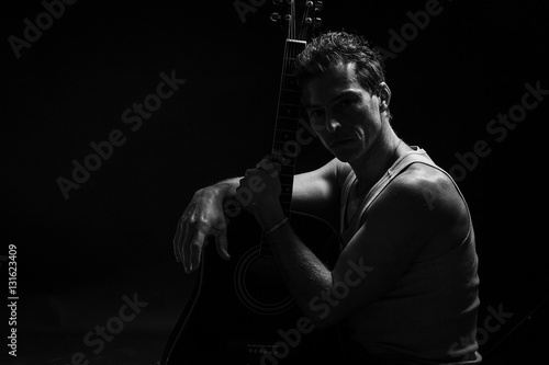 Low key portrait of man with his guitar
