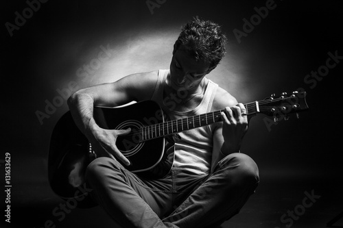 Póster Young caucasian man play a acoustic guitar