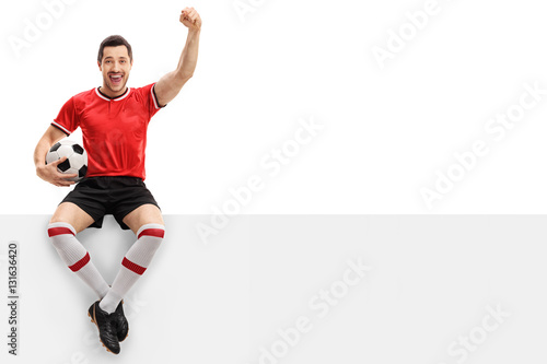 Excited football player sitting on a panel and gesturing happiness