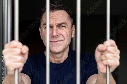 Middle aged blue eyed man incarcerated Poster