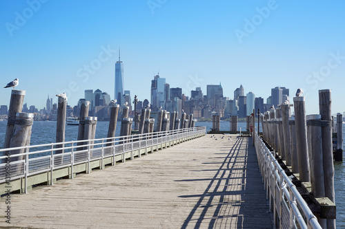 New York city skyline and empty pier with seagulls, sunlight Poster