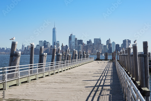 New York city skyline and empty pier with seagulls in a sunny day Poster