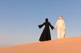Couple dressed in traditional arabic dress in desert of Dubai, UAE.