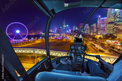 Helicopter cockpit aerial view of cityscape in Hong Kong, Central District, with Observation Ferris Wheel at Victoria Harbour illuminated at night