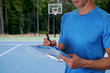Basketball trainer with workout plan close up on basketball field. Team sport, fitness and healthy life style concept.