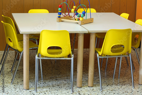 yellow chairs with a toy over the desk inside the nursery