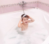 Adorable baby  with soap suds on hair taking bath. Closeup portr