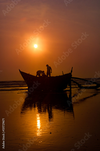 Poster Fishermen preparing a boat to start fishing with sunset at background