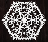 snowflake cut out of paper on dark brown table