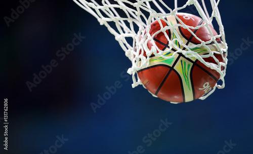 Fotobehang Basketbal Basketball ball goes through the basket, net