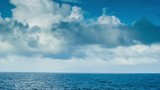 A Moving Ocean Scape seen from a Sea Going Vessel with Majestic Clouds and Blue Water