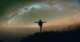 Girl doing yoga pose under Milky Way on mountain.