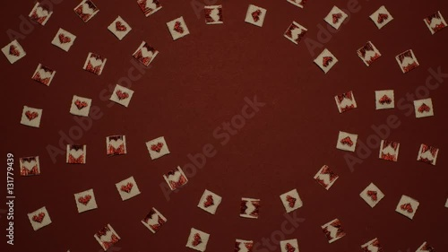 St. Valentine`s day stop motion animation of a spiral formed in small cloth squares with red hearts on them on dark red background © gingerstock