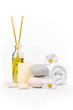 Spa decoration with stones, daisies, candles and a bottle with massage oil on a white background