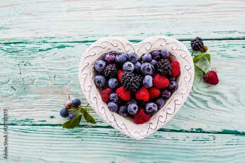Forest fruits in a bowl in the shape of a heart on a wooden table.