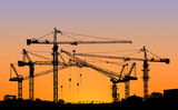 silhouette of construction tower crane with sunset sky backgroun