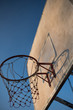 Old basketball hoop with blue sky.