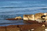 вдоль берега  моря лежат камни и валуны разной величины