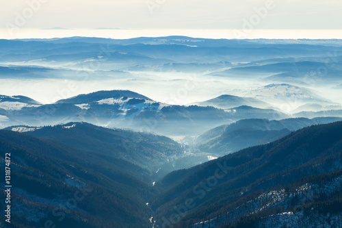 Plakát Mountains valley with gentle haze above it