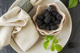 Fresh blackberries in ceramic portioned plates on a light wooden background with table linens. Top view. Style hygge