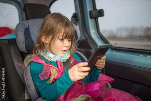Poster enfant dans son siège auto jouant avec une tablette