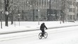 Person Riding Bicycle Through Snow Storm on City Street