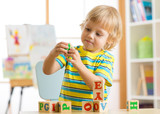 Fototapety child boy playing with block toys and learning letters