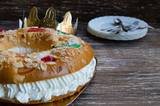 Roscon de reyes (kings' ring), typical dessert eaten in Spain to celebrate Epiphany or Dia de Reyes Magos (Three Kings' Day). Spanish Christmas  cake with  fruits, nut and icing on wooden background