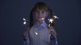 Cute little ginger girl in the vest holding the sparkles in the darkness and smiling