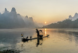 Cormorant fisherman stands on the ancient bamboo boat in the sunrise - The Li River, Xingping, China