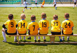Fototapety Young Football Players. Young Soccer Team Sitting on Wooden Bench. Soccer Match For Children. Young Boys Playing Tournament Soccer Match. Youth Soccer Club Footballers