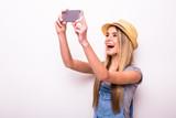 Cheerful girl in cap making selfie on smartphone
