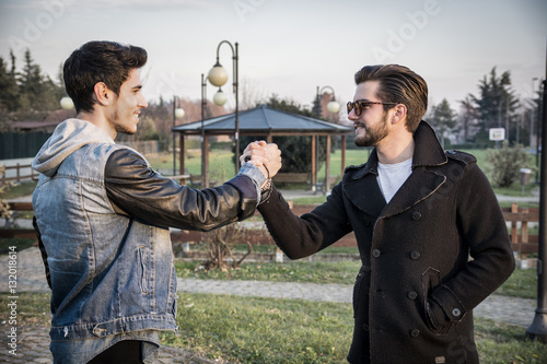 Poster Two handsome casual trendy young men greeting outdoors in an urban park gripping