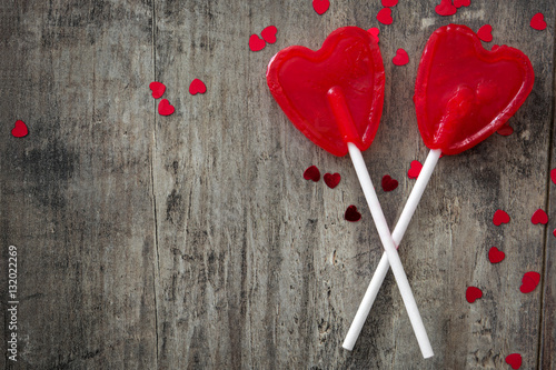 Red lollipops with heart shape on wooden background Poster