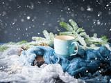 Mug of coffee and milk on dark blue winter background. Hot drink still life with falling snow