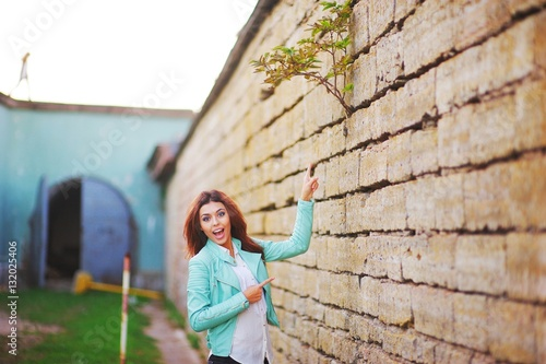 Poster Young cute smiling girl in turquoise jacket and jeans stands near a stone wall a