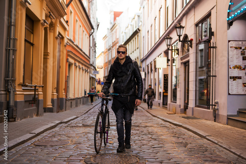 Poster Hipster man in the city walking down the street with bicycle
